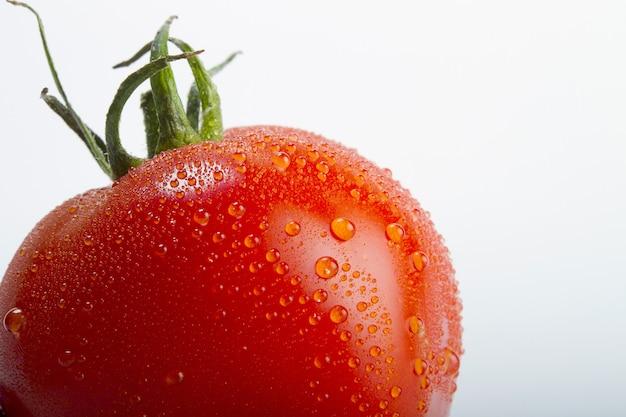 Colpo del primo piano di un pomodoro fresco con le gocce di acqua su esso isolato su una priorità bassa bianca