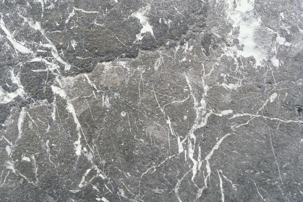 Colpo del primo piano di un terreno in pietra con diversi modelli di bianco sparsi intorno ad esso
