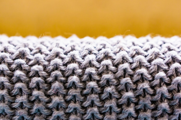 Colpo del primo piano di un tessuto lanuginoso grigio con uno sfondo marrone sfocato