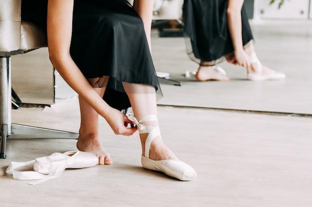 Colpo del primo piano di una ballerina che toglie le scarpe di balletto che si siedono sul pavimento