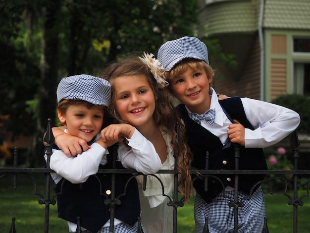 Colpo del primo piano di una bambina carina e due ragazzi in costumi identici in piedi dietro il recinto
