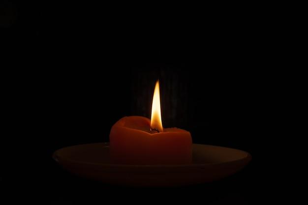 Colpo del primo piano di una candela accesa nel buio