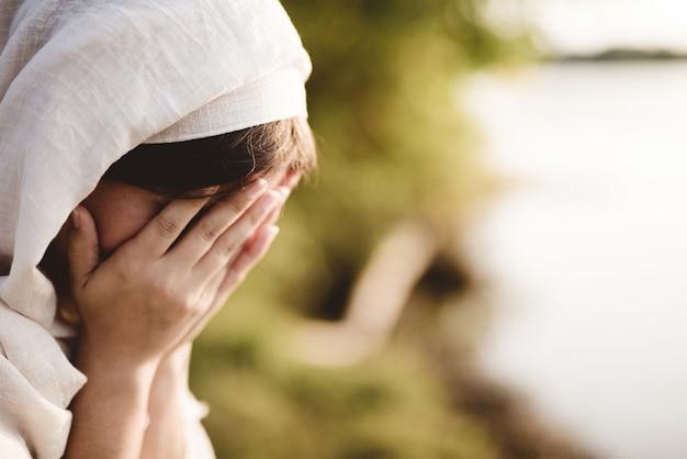 Colpo del primo piano di una femmina che indossa un abito biblico che prega con uno sfondo sfocato