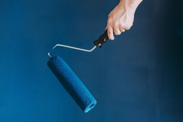 Colpo del primo piano di una femmina che usando i rulli di pittura con il blu di colore