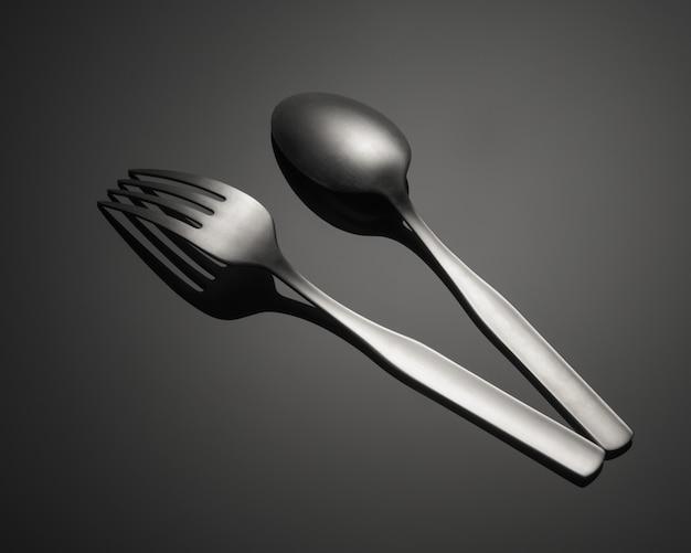 Colpo del primo piano di una forchetta del metallo e di un cucchiaio isolati su una tabella grigia