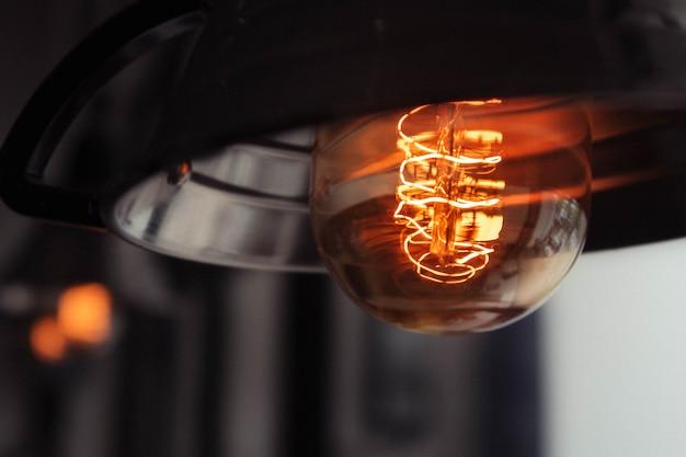 Colpo del primo piano di una grande lampadina accesa con uno sfondo sfocato