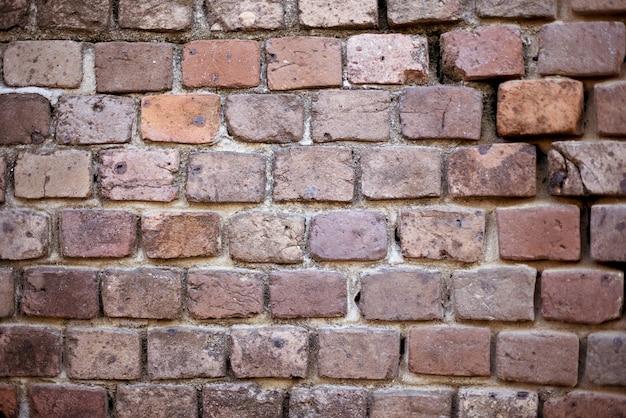 Colpo del primo piano di una parete di pietra impilata rossa