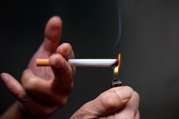 Colpo del primo piano di una persona che accende una sigaretta