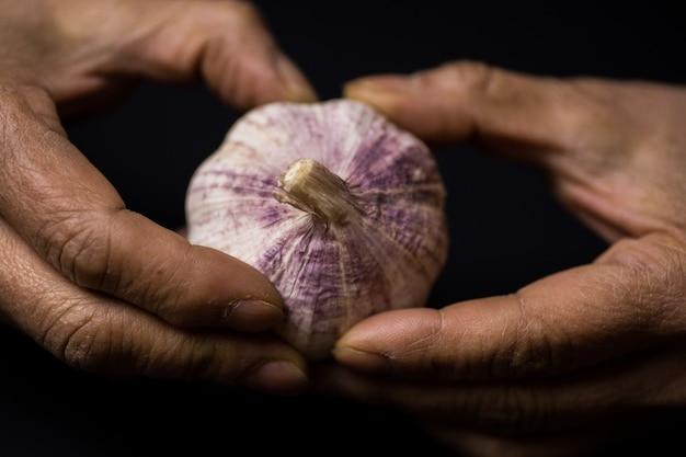 Colpo del primo piano di una persona che sbuccia l'aglio