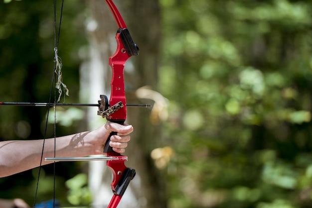 Colpo del primo piano di una persona che sostiene e arco e freccia