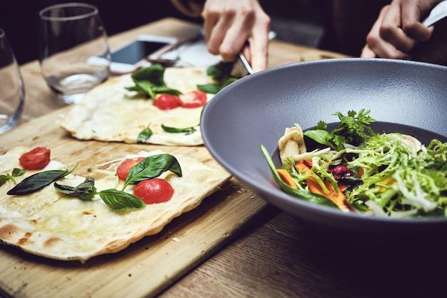 Colpo del primo piano di una persona che taglia la verdura e fa un'insalata