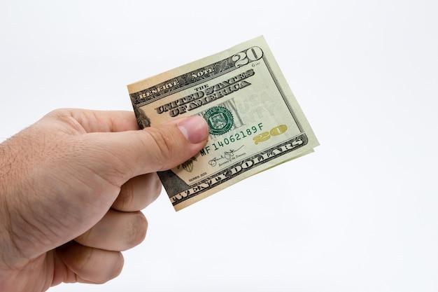 Colpo del primo piano di una persona che tiene una fattura del dollaro sopra un bianco