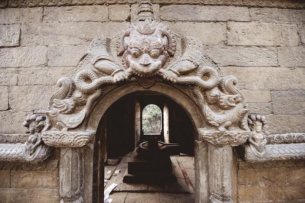 Colpo del primo piano di una porta ad arco con scolpire in un tempio indù in nepal