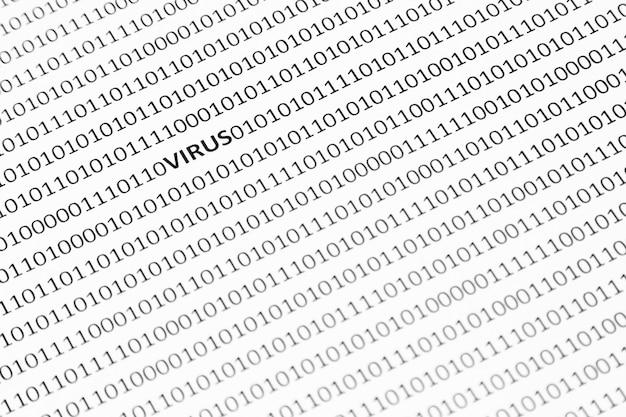 Colpo del primo piano di una superficie bianca con virus e uno e zero sono scritti su di esso