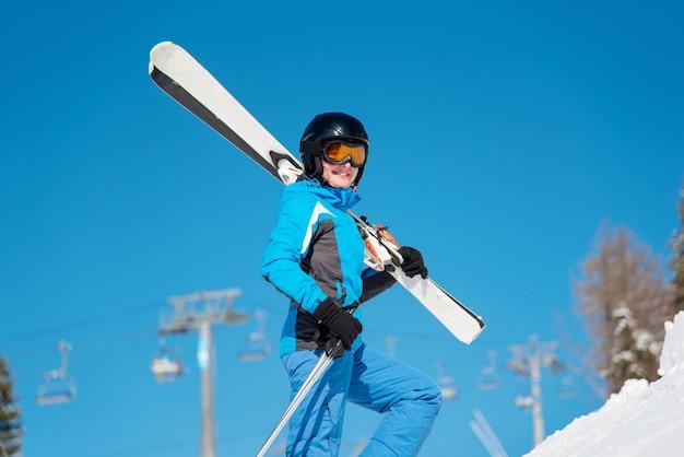 Colpo del primo piano di uno sciatore femminile allegro che trasporta i suoi sci che sorridono alla macchina fotografica