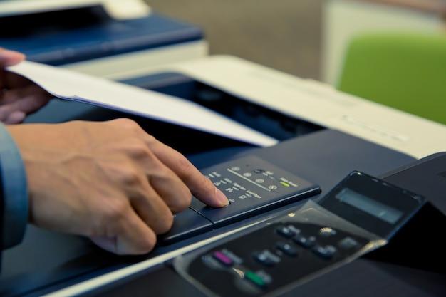 Colpo del primo piano gli uomini d'affari stanno usando le fotocopiatrici.