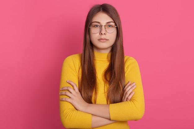 Colpo dell'interno della femmina seria o arrabbiata che sta con le sue armi attraversate. la ragazza con capelli lunghi veste la camicia gialla