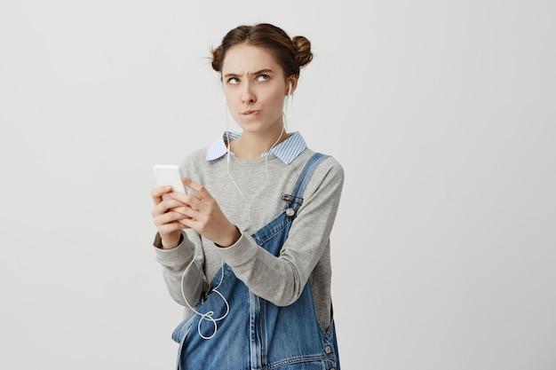 Colpo dell'interno della ragazza adulta risentita che posa con il suo cellulare in mani che morde le sue labbra nell'irritazione. persona di sesso femminile che viene offesa con il testo ricevuto durante il social network. reazioni umane
