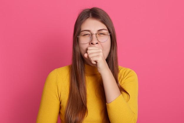 Colpo dell'interno della ragazza che sbadiglia indossando occhiali e camicia gialla casual