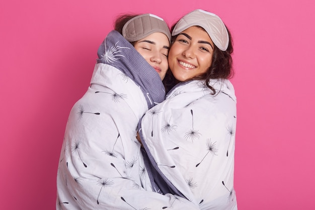 Colpo dell'interno delle donne sorridenti con le maschere di sonno, indossando la coperta sta la contrattazione isolata sopra è aumentato