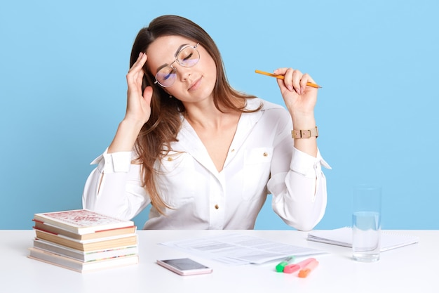 Colpo dell'interno di giovane donna di affari mora esaurita che si siede nell'ufficio allo scrittorio bianco, tiene gli occhi chiusi, toccando la sua fronte, sembra malato e stanco di lavorare con le carte. concetto di persone e lavoro.