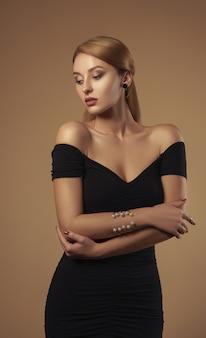Colpo dello studio della donna attraente che porta fuori il vestito nero dalle spalle - colpo dello studio di bellezza di bella donna in vestito nero