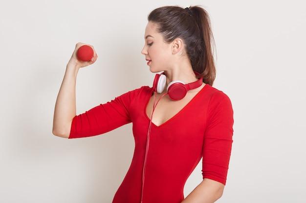Colpo dello studio della donna caucasica in buona salute con risolvere delle teste di legno isolato su bianco. signora attrractive che mostra le sue mascotte, osservando sul suo braccio, forma fisica, palestra, concetto di cura sana.