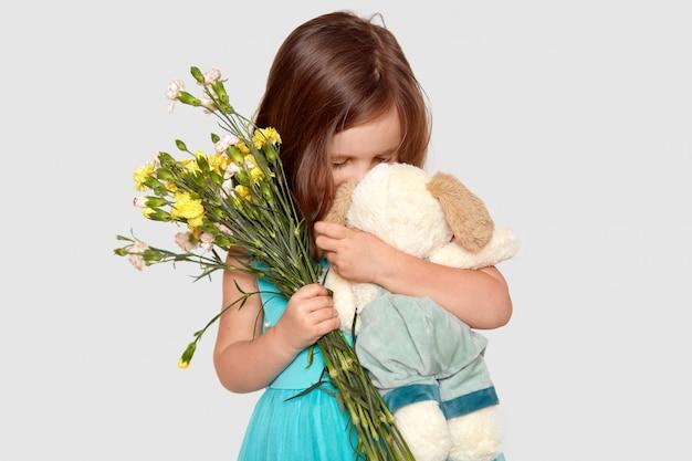 Colpo di adorabili piccoli giochi da bambini femminili con il suo giocattolo preferito, tiene fiori, gode di ricevere presente, vestito in abiti festivi, isolato su bianco. bambini e stile di vita