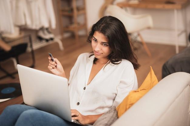 Colpo di alta vista della donna in possesso di una carta di credito e usando il suo computer portatile