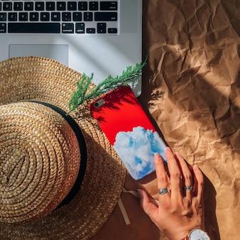 Colpo di alto angolo della mano di una persona con anelli d'argento vicino a un computer portatile, un telefono e un cappello