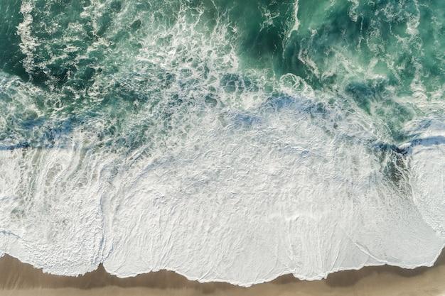 Colpo di alto angolo delle onde blu dell'oceano che spruzzano alla riva