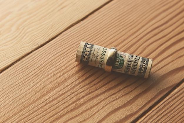 Colpo di alto angolo di banconote da un dollaro arrotolate in un anello d'oro su una superficie di legno