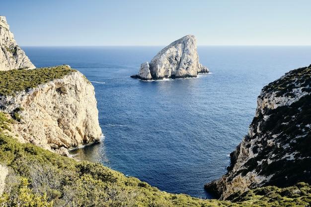 Colpo di alto angolo di scogliere erbose vicino al mare con una roccia in lontananza