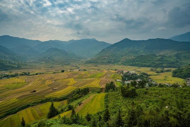 Colpo di alto angolo di un bellissimo paesaggio verde con alte montagne e case sotto le nuvole di tempesta