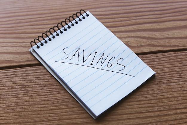 Colpo di alto angolo di un piccolo taccuino con la parola risparmio scritto su di esso su una superficie di legno