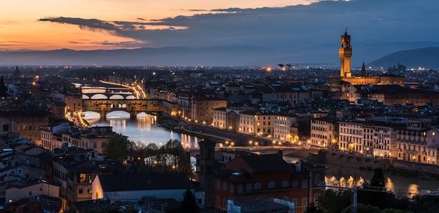 Colpo di alto angolo di un sacco di edifici con luci e un ponte di sera