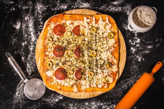 Colpo di alto angolo di una deliziosa pizza fatta in casa su una tavola di legno e una ciotola di farina