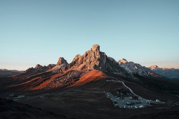 Colpo di alto angolo di una formazione rocciosa marrone e molte macchine parcheggiate sotto il cielo blu la sera