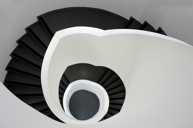 Colpo di alto angolo di una scala nera che scende circondato da pareti bianche