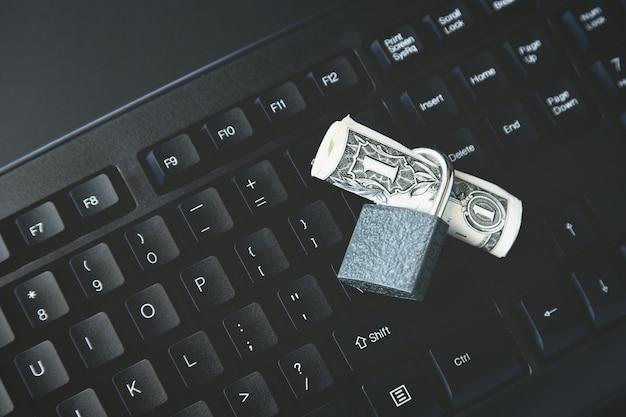 Colpo di alto angolo di una serratura intorno a una banconota da un dollaro su un computer portatile nero