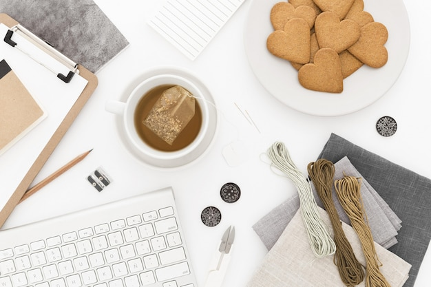 Colpo di alto angolo di una tastiera, una tazza di tè e biscotti, alcuni thread e documenti su una superficie bianca