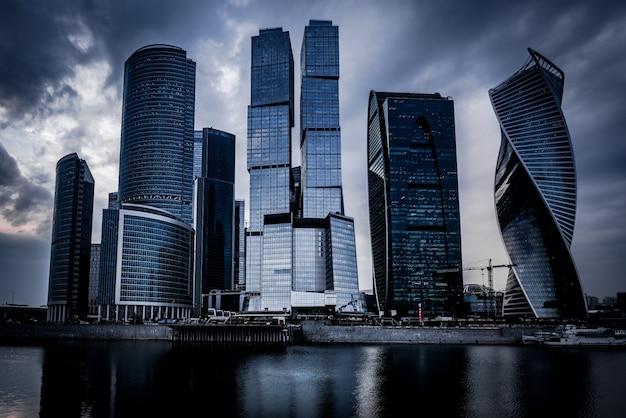 Colpo di angolo basso dei grattacieli grigi davanti al fiume sotto il cielo nuvoloso scuro