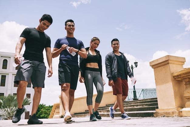 Colpo di angolo basso del gruppo atletico che cammina all'aperto dopo l'allenamento congiunto