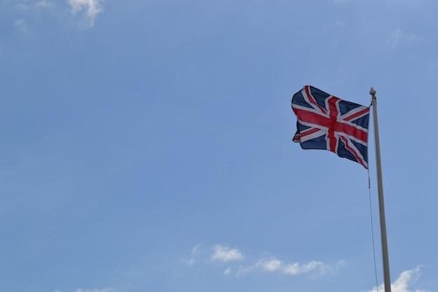 Colpo di angolo basso della bandiera della gran bretagna su un palo sotto il cielo nuvoloso