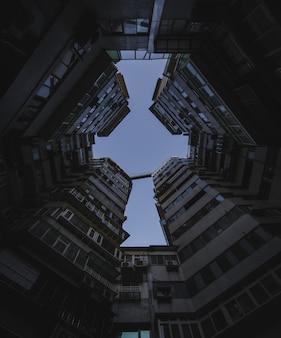 Colpo di angolo basso delle costruzioni di appartamento alte sotto il cielo scuro