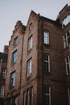 Colpo di angolo basso di architettura marrone del mattone con un cielo bianco