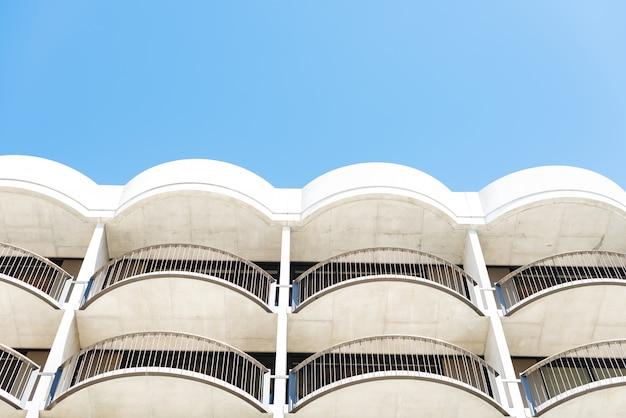 Colpo di angolo basso di costruzione architettonica bianca con i balconi