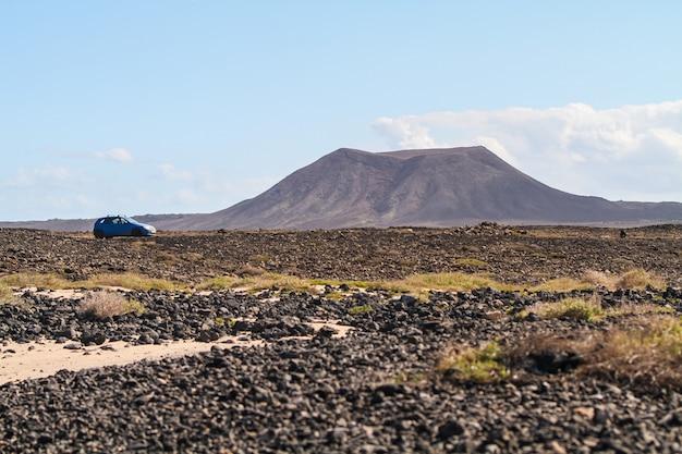 Colpo di angolo basso di un'automobile blu parcheggiata accanto a una collina a fuerteventura, isole canarie