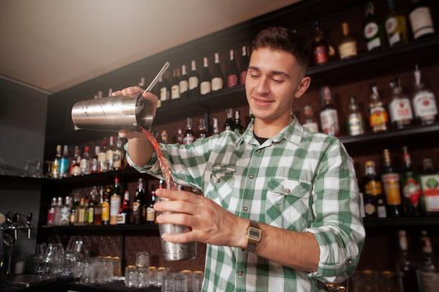 Colpo di angolo basso di un barista allegro bello preparare un cocktail, copia spazio