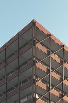 Colpo di angolo basso di un edificio moderno nel mezzo della città sotto il cielo limpido